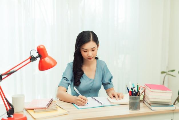 Een jonge vrouwelijke student zit aan de tafel, met behulp van tablet tijdens het studeren.