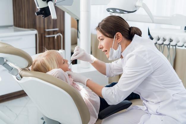 Een jonge vrouwelijke tandarts die een grondig onderzoek van de tanden van haar patiënt uitvoert