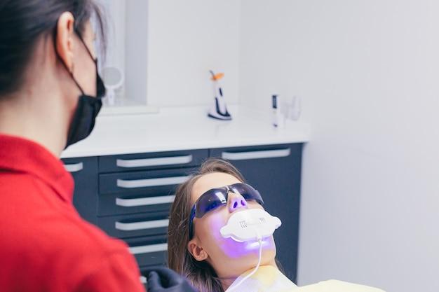 Een jonge vrouwelijke tandarts praat met een patiënt voordat hij begint met een behandeling of een procedure in een moderne tandheelkundige kliniek