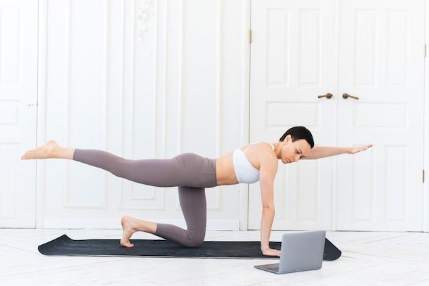Een jonge vrouwelijke trainer geeft yoga op afstand via internet met haar laptop