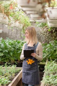 Een jonge vrouwelijke tuinman houdt in het voorjaar een overzicht van bloemen in een kas bij.