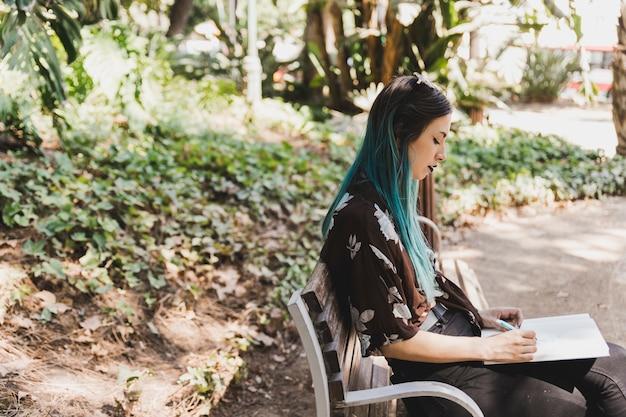 Een jonge vrouwenzitting op banktekening in notitieboekje