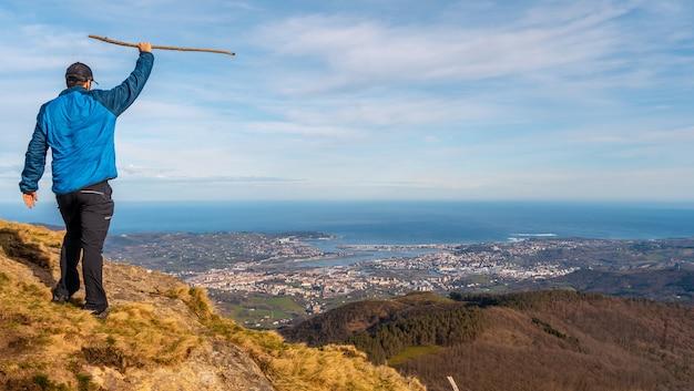 Een jonge wandelaar kijkt naar het uitzicht op de steden hondarribia en hendaya vanuit de bergen van aiako harria of peã ± as de aya, guipãºzcoa