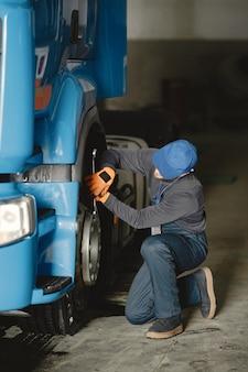 Een jonge werknemer controleert het wiel. truck defect. servicewerk.