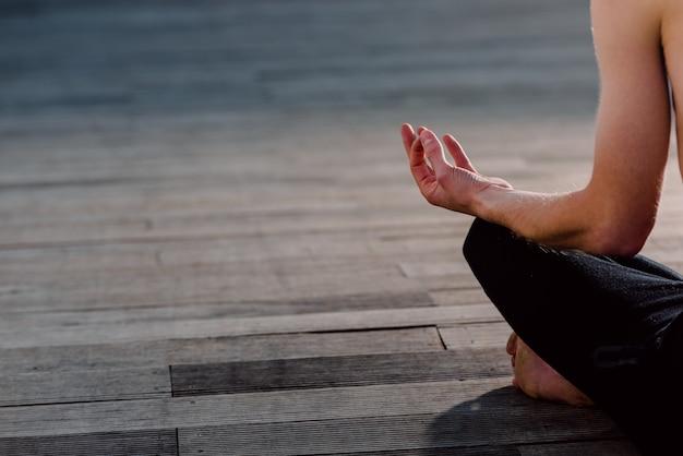 Een jonge yogi legt zijn ontspannen handen op zijn knieën tijdens de lotus asana, zittend op hout. kopieer ruimte