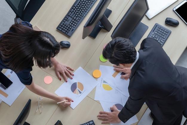 Een jonge zakenman beschrijft een baan voor een mooie aziatische vrouw in een donkerblauw pak aan de balie in een modern kantoor.