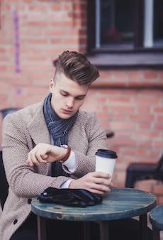 Een jonge zakenman controleert de tijd op zijn polshorloge aan een tafel met koffie