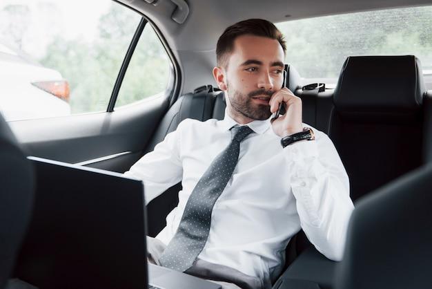 Een jonge zakenman die aan laptop werkt en op de telefoon spreekt terwijl het zitten in de rug van de auto. werkt in beweging, waardeert zijn tijd
