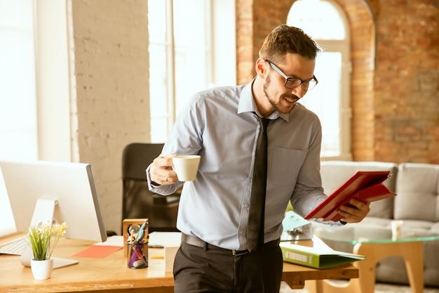 Een jonge zakenman die na promotie op kantoor werkt
