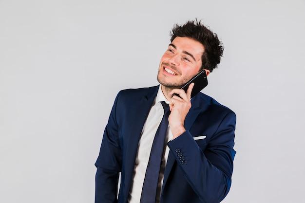 Een jonge zakenman die op mobiele telefoon tegen grijze achtergrond spreekt