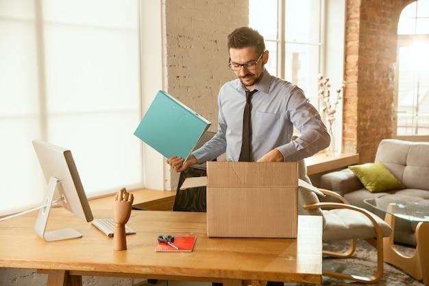 Een jonge zakenman die zich op kantoor beweegt en een nieuwe werkplek krijgt.