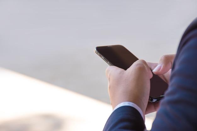 Een jonge zakenman draagt een blauw pak met behulp van een smartphone in een buitenlocatie
