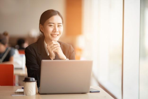 Een jonge zakenman draagt een zwart pak aan het bureau.