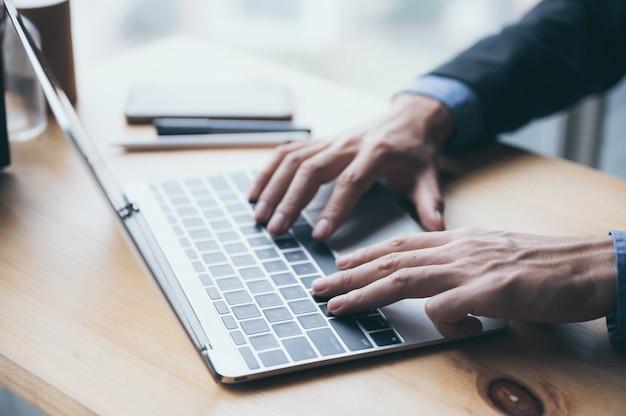 Een jonge zakenman in een zwart pak werkt vanuit een privéwoning aan een laptop en werkt online om het risico op virusinfectie te verkleinen.