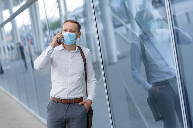 Een jonge zakenman is praten aan de telefoon in een medisch masker op een modern kantoorgebouw.