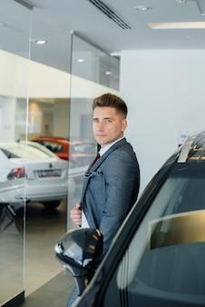 Een jonge zakenman kijkt naar een nieuwe auto in een autodealer. een auto kopen.