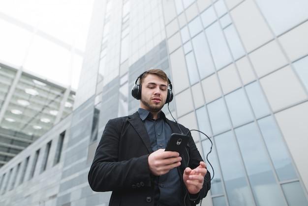 Een jonge zakenman luistert naar muziek in een koptelefoon en gebruikt een smartphone terwijl hij door de stad loopt.