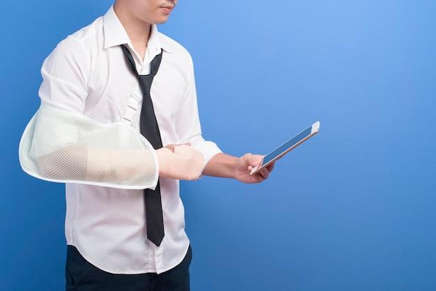 Een jonge zakenman met een gewonde arm in een mitella met behulp van een tablet over blauwe muur, verzekering en gezondheidszorg concept