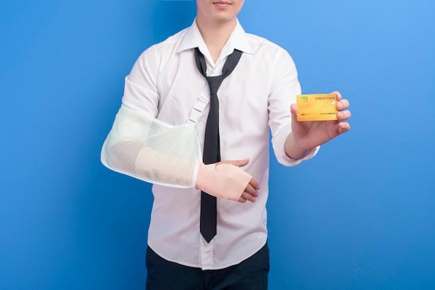 Een jonge zakenman met een gewonde arm in een mitella met een creditcard of medische verzekeringskaart over blauwe achtergrond in studio, verzekering en gezondheidszorg concept