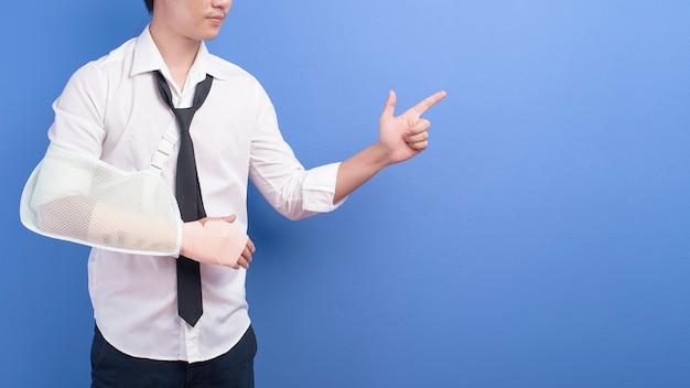 Een jonge zakenman met een gewonde arm in een mitella over blauwe muur