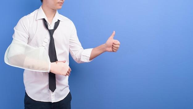 Een jonge zakenman met een gewonde arm in een slinger over blauwe muur, verzekering en gezondheidszorgconcept
