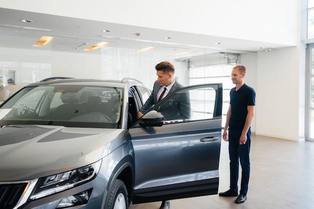 Een jonge zakenman met een verkoper kijkt naar een nieuwe auto in een autodealer. een auto kopen.