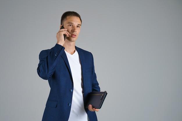 Een jonge zakenman met kort haar in een blauw jasje en een wit t-shirt houdt een telefoon in zijn hand en praat tegen een grijze achtergrond