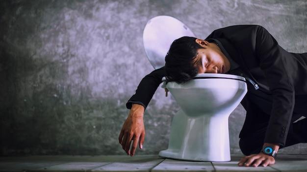 Een jonge zakenman slaapt in de badkamer