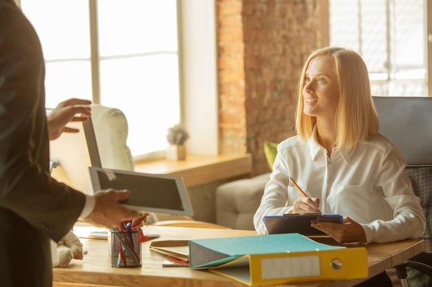 Een jonge zakenvrouw die zich op kantoor beweegt en een nieuwe werkplek krijgt