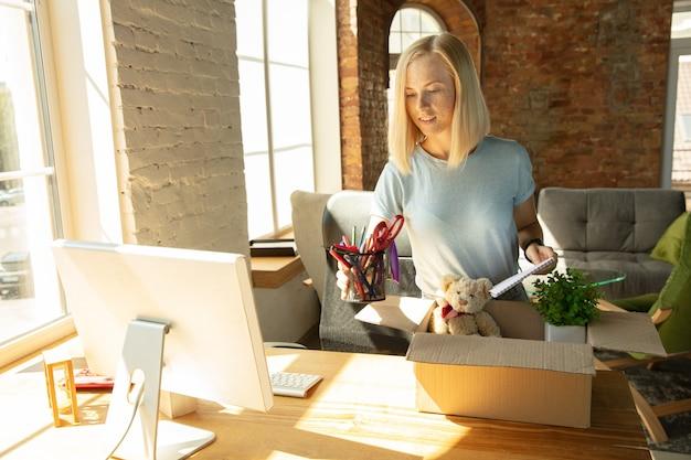 Een jonge zakenvrouw die zich op kantoor beweegt en een nieuwe werkplek krijgt.