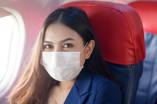 Een jonge zakenvrouw draagt een beschermend masker aan boord in het vliegtuig, reist onder covid-19 pandemie, veiligheidsreizen, sociaal afstandsprotocol
