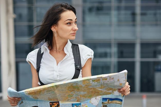 Een jonge zakenvrouw op zoek naar iets op de kaart zittend op de bank