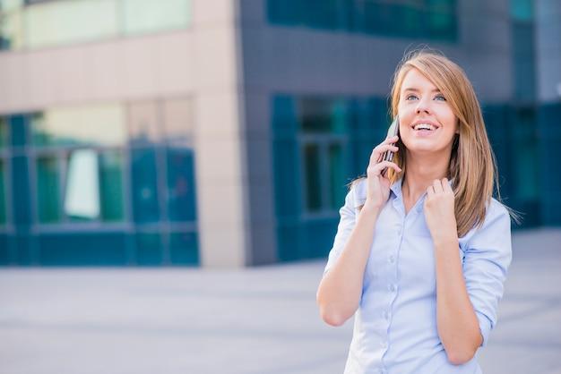 Een jonge zakenvrouw praten over haar telefoon terwijl ze voor een kantoorblok staan
