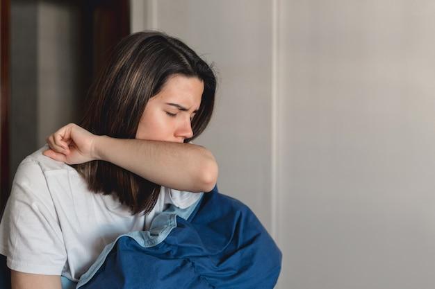 Een jonge zieke vrouw die besmet is met het coronavirus hoest in haar bovenarm terwijl ze zich bedekt met een blauwe deken in haar huis