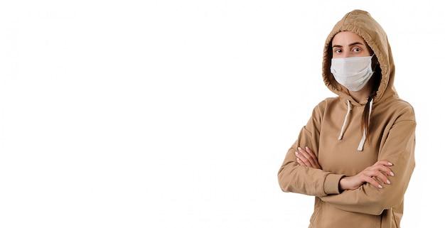 Een jonge zieke vrouw in een beschermend medisch masker, in een trui met een kap.