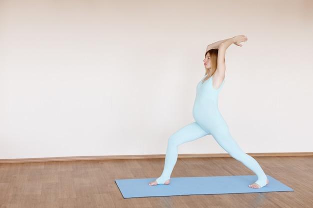 Een jonge zwangere vrouw beoefent yoga in een blauw pak op een beige achtergrond