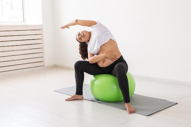 Een jonge zwangere vrouw die ontspanningsoefeningen doet met een fitnessbal terwijl ze op een mat zit en haar buik vasthoudt