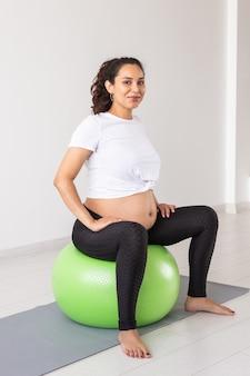 Een jonge zwangere vrouw die ontspanningsoefeningen doet met een fitnessbal terwijl ze op een mat zit