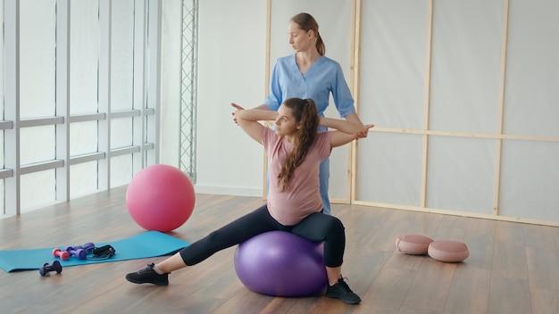 Een jonge zwangere vrouw doet oefeningen met een gezondheidswerker in een kliniek. het lichaam voorbereiden op de bevalling. gezondheids- en sportconcept tijdens de zwangerschap.