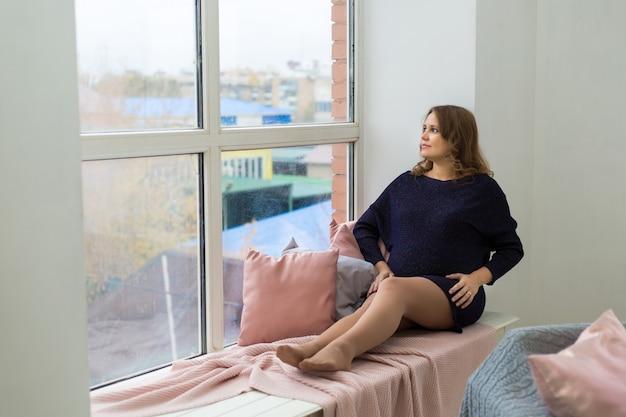 Een jonge zwangere vrouw in een blauwe jurk zit bij een groot raam met haar handen op haar buik. wachten op een wonder