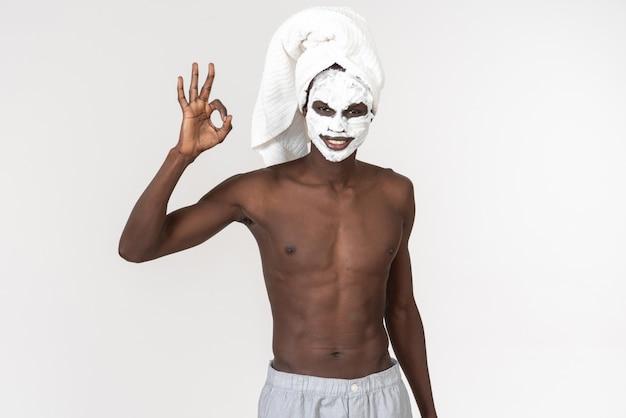 Een jonge zwarte man met een badhanddoek om zijn middel