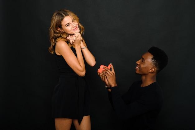Een jonge zwarte man stelt zijn blanke vriendin voor terwijl hij op één knie staat.