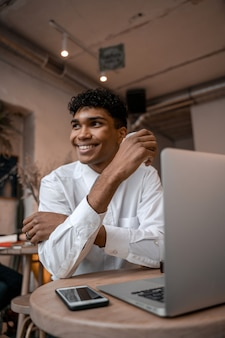 Een jonge zwarte man zit aan tafel met een laptop, drinkt thee en gebruikt een smartphone. de man in het café. werk buiten kantoor, werk op afstand of studieconcept. verticale foto.