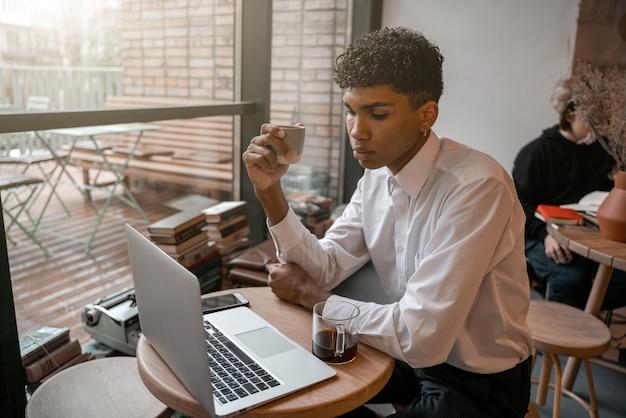 Een jonge zwarte man zit aan tafel met een laptop, drinkt thee en gebruikt een smartphone. de man in het café. werk buiten kantoor, werk op afstand of studieconcept.