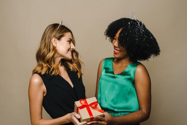 Een jonge zwarte vrouw geeft haar blanke vriendin een vakantiegift.