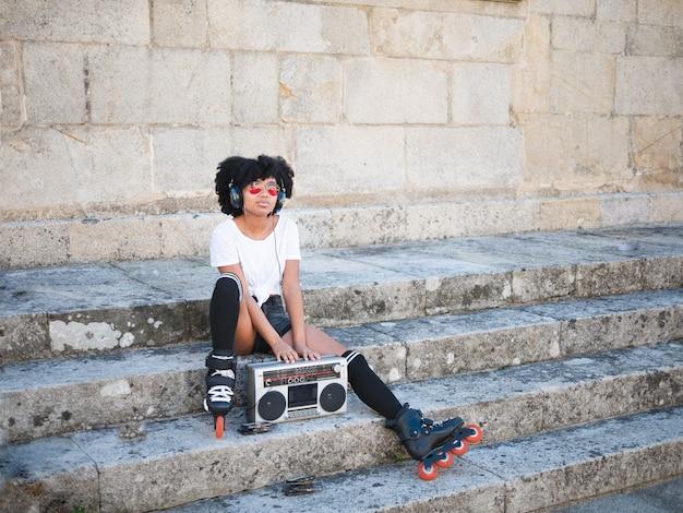 Een jonge zwarte vrouw zat op een trap op straat naar muziek te luisteren met een koptelefoon en een vintage cassette-radio