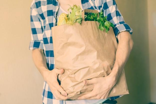Een jongeman in casual kwam thuis uit een voedselwinkel en kocht een verse kruidenierswinkel in een papieren zak