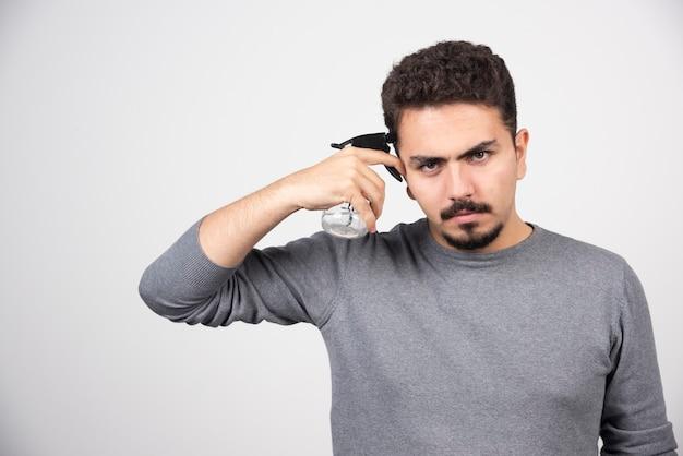 Een jongemannenmodel met plastic spuitfles.
