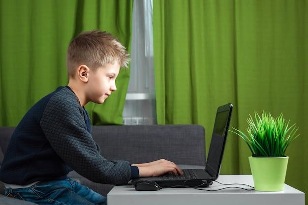 Een jongen achter een laptop speelt games of kijkt naar een video