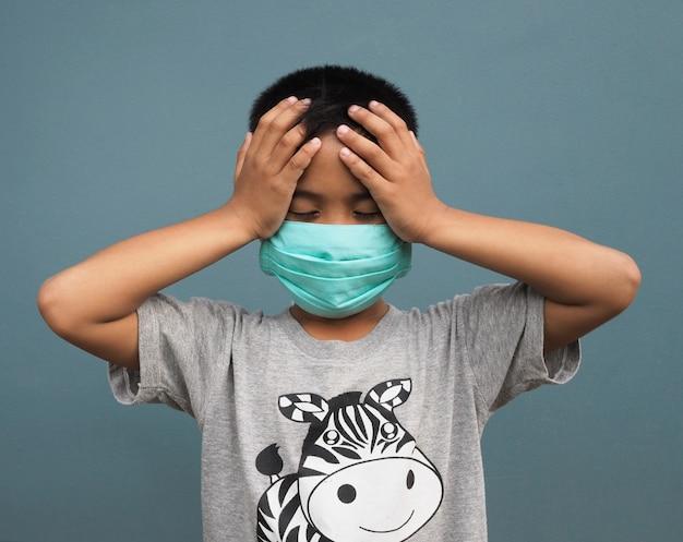 Een jongen die een beschermend masker draagt en zijn hand in het hoofd houdt vanwege veel hoofdpijn.